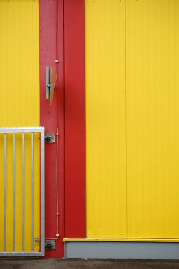 A colorful and striking sidewall of a shopping center with a part of an access gate and a road sign.