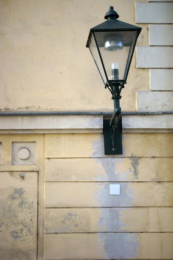 A nostalgic wall lamp and lantern on a prominent wall.