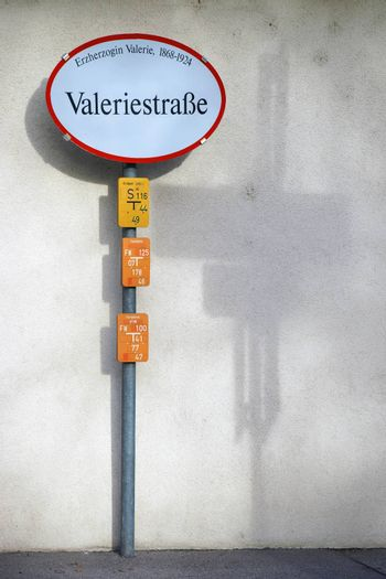 A nostalgic road sign of Archduke Valerie Street in Austria casts a shadow on the wall.