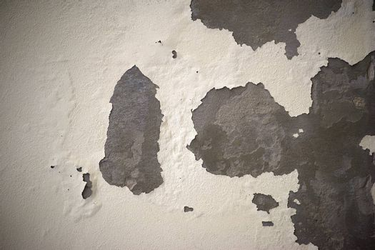 The closeup of a plaster wall where the plaster gets cracks.