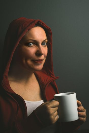 Beautiful satisfied red hooded woman drinking coffee