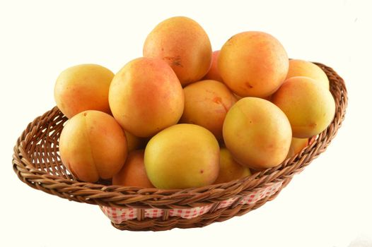 Apricots in a basket isolated on white background.