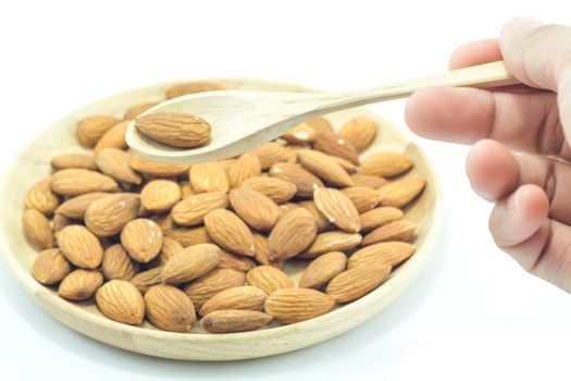 Hand on spoon of almond isolated on white background, stock photo