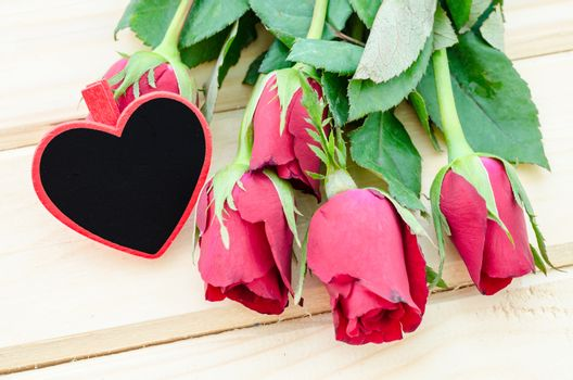 Blank wooden tag heart shape with red roses.
