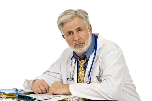 Horizontal shot of a tired doctor sitting at his desk.  Shot on white background.