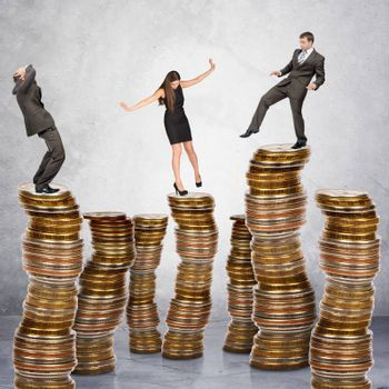 Business people standing on coins stack on grey background