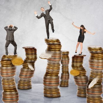 Business people standing on coins piles on grey background