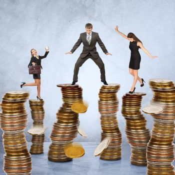 Business people standing on stacks of coins on grey background