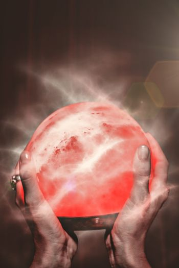 Composite image of fortune teller holding crystal ball