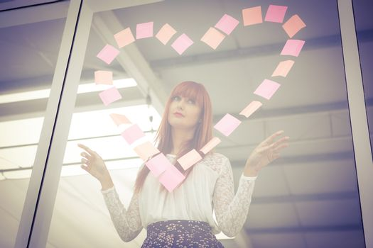 Smiling hipster woman doing a heart in post-it in office