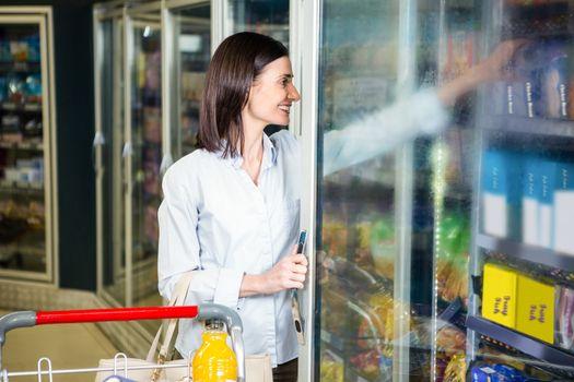Smiling woman opening fridge