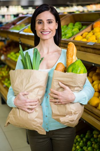 Smiling woman holding grocery bag