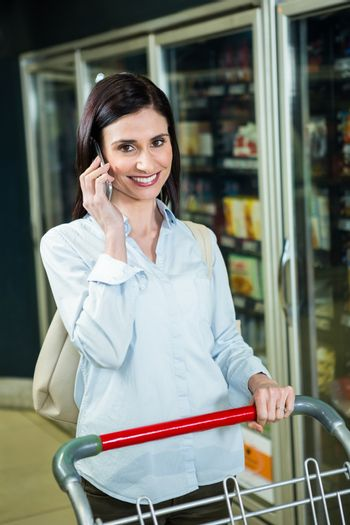 Smiling woman on phone in aisle