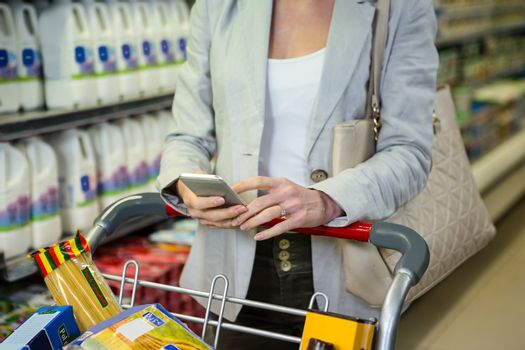Woman using her smartphone in aisle