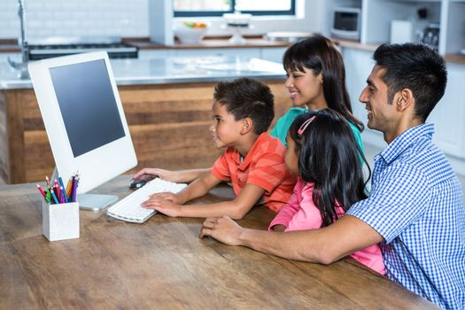 Side view of happy family using computer in kitchen