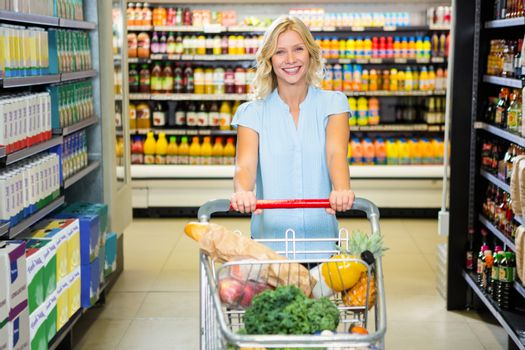 Smiling woman pushing trolley in aisle