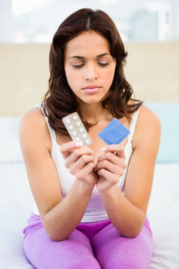 Concerned woman looking at contraception