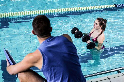 Smiling fit woman doing aqua aerobics
