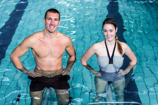 Smiling couple doing aqua aerobics