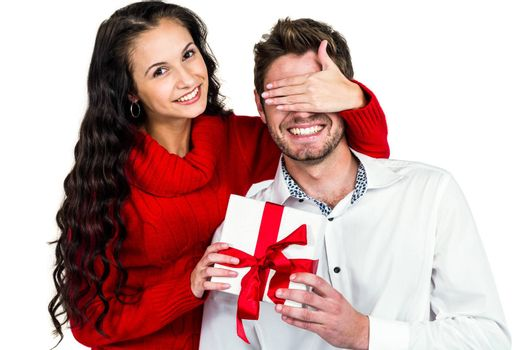 Young woman covering eyes of partner holding gift on white screen