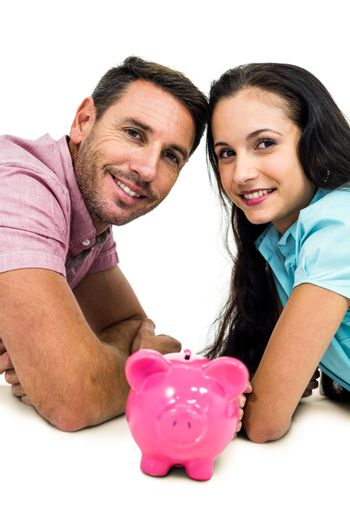 Smiling couple laying on the floor face to face with piggybank