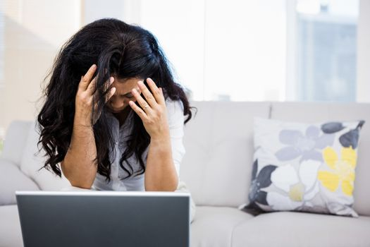 Concerned woman sitting at home