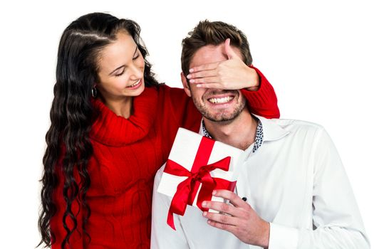 Smiling woman covering eyes of partner holding gift on white screen