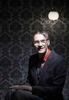 Crazy maniac man sitting in the dark room. Vertical photo