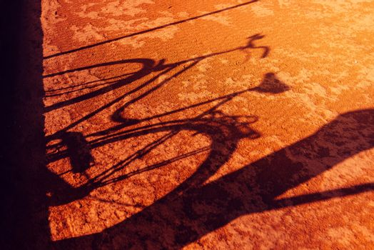 Vintage bicycle shadow on red clay ground