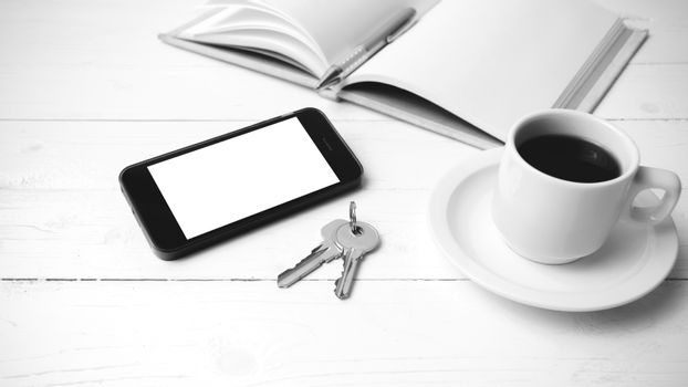 coffee cup with phone, key and open notebook black and white col
