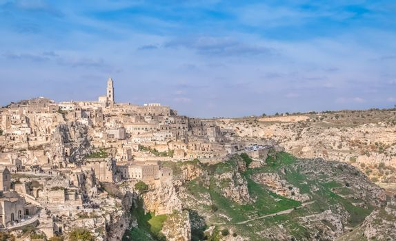 panoramic view of typical stones (Sassi di Matera) and church near gravina of Matera UNESCO European Capital of Culture 2019 on blue sky