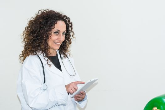 Doctor with curly hair and blacks and with green eyes, use a tablet of white color. The new technologies used in the medical field.