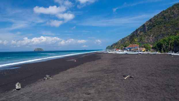 Junks on the beach of black sand on the island of Bali in Indonesia. Summer sunny day.