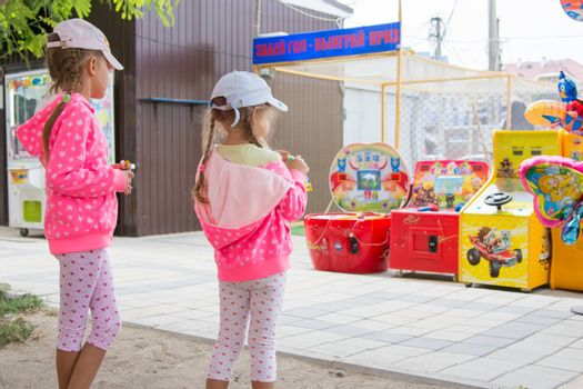 Anapa, Russia - September 14, 2015: Two girls eating chocolate with interest looking at the childrens slot machines