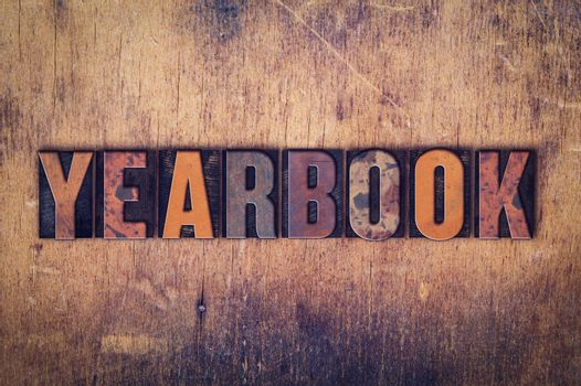 "The word ""Yearbook"" written in dirty vintage letterpress type on a aged wooden background."