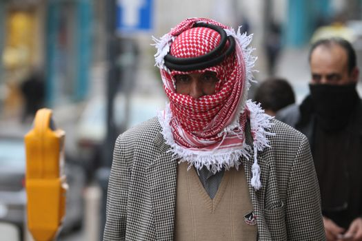 WEST BANK, Bethlehem: A man wearing a headscarf walks on a street, in the Palestinian city of Bethlehem, on January 19, 2016, as a sandstorm hits Israel and West Bank, causing air pollution. A low-pressure system over the Mediterranean has driven the dust northeast from Egypt and the Sinai Peninsula.