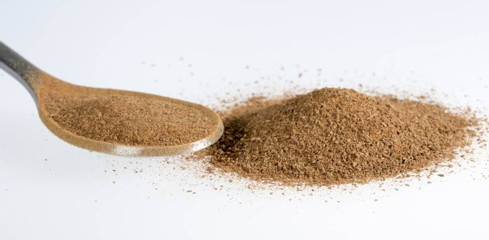 Cinnamon Powder Close Up on a tablespoon and in a pile.
