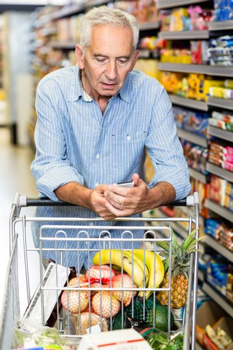 Senior man using phone at grocery store