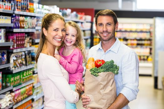 Smiling family with grocery bag at the supermarket