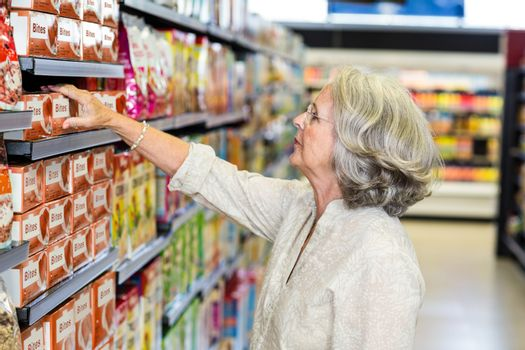 Senior woman picking food from aisle
