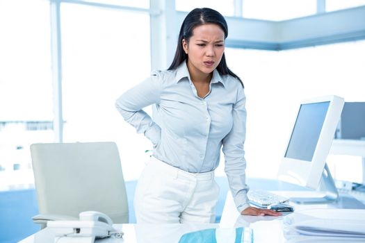 Frowning businesswoman with back ache