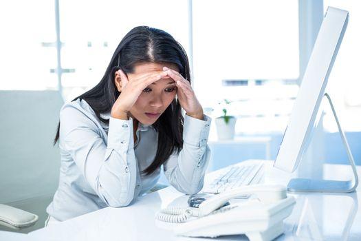 Unsmiling businesswoman with hands on head