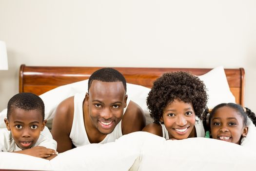 Cute family resting on bed