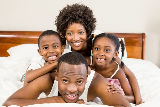 Happy family lying in bed together at home