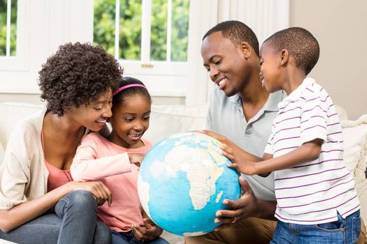 Smiling family sitting on the couch together using a globe