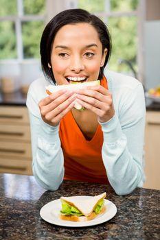Day dreaming brunette eating sandwich