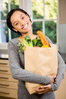 Smiling brunette holding grocery bag
