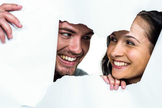 Couple peeking through torn paper