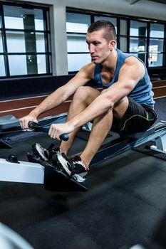 Muscular man using rowing machine