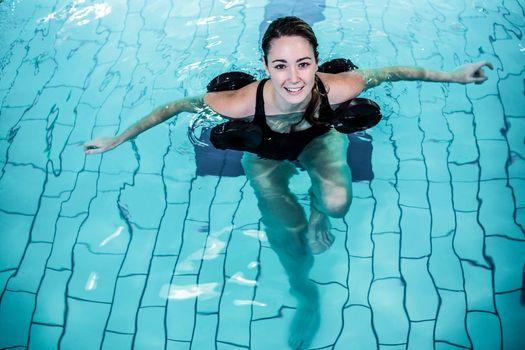 Fit smiling woman doing aqua aerobics